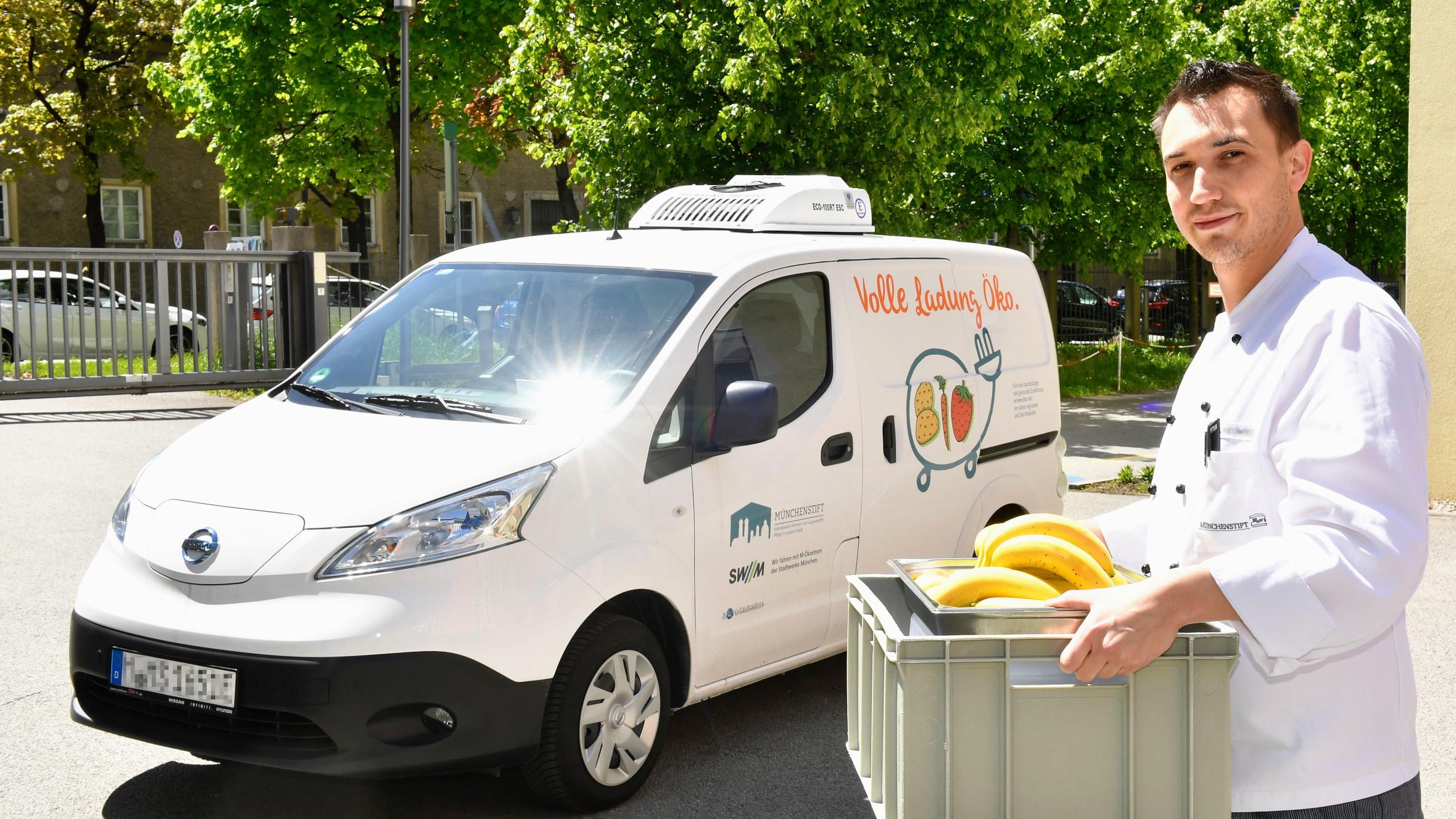 Mitarbeiter der Küche beim beladen eines neuen e-mobilen Küchen-Lieferfahrzeugs