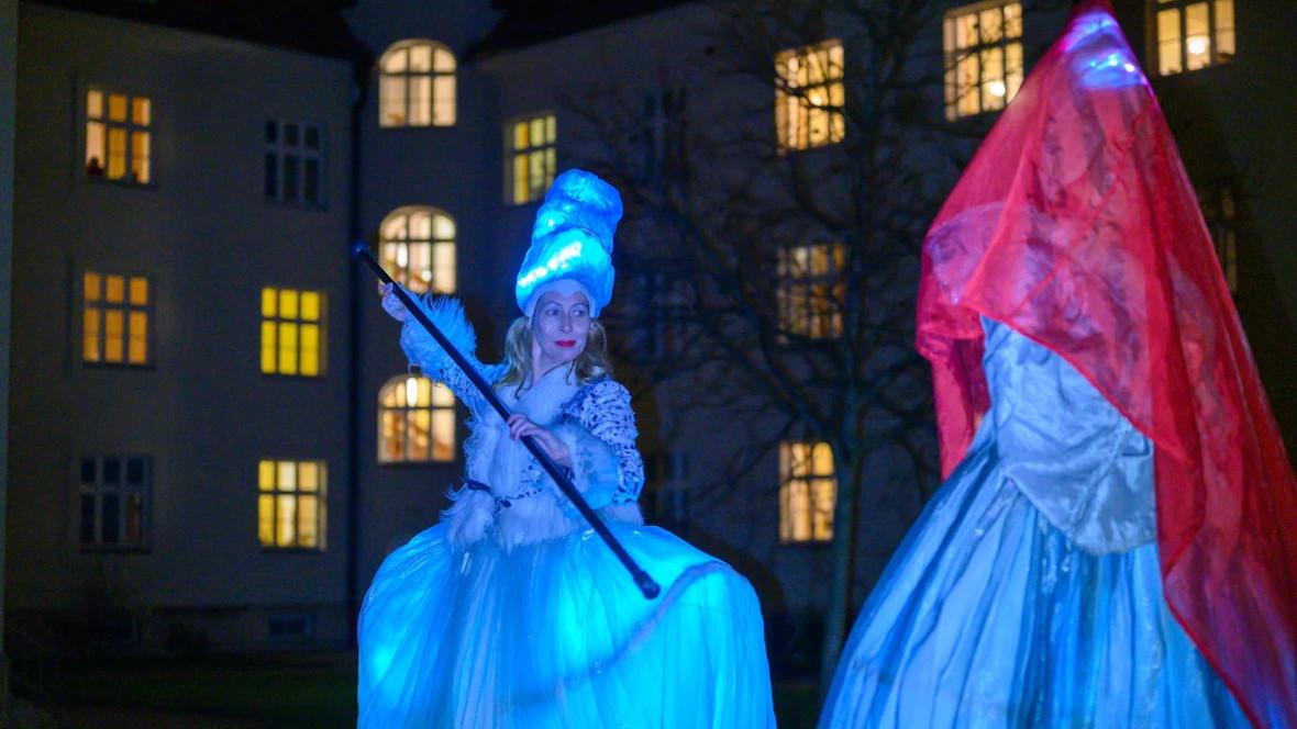 Stelzentänzerinnen mit beleuchteten Kostümen bei Nacht im Innenhof des Hauses Heilig Geist