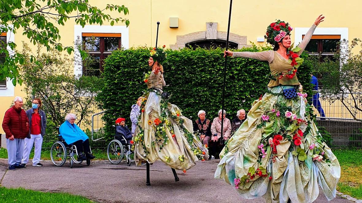 Stelzentänzerinnen mit blumigen Kostümen im Garten des Hauses an der Rümannstraße